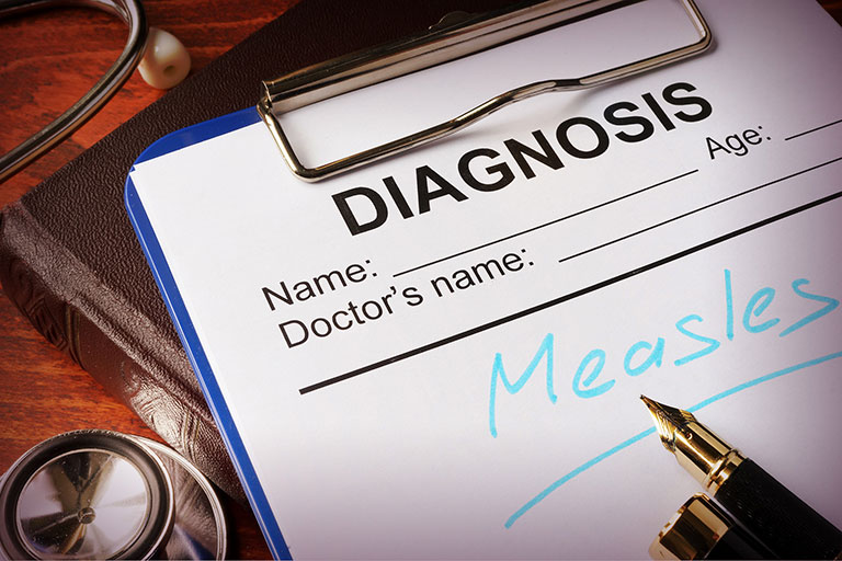 A photo a diagnosis form on a clipboard - diagnosis Measles