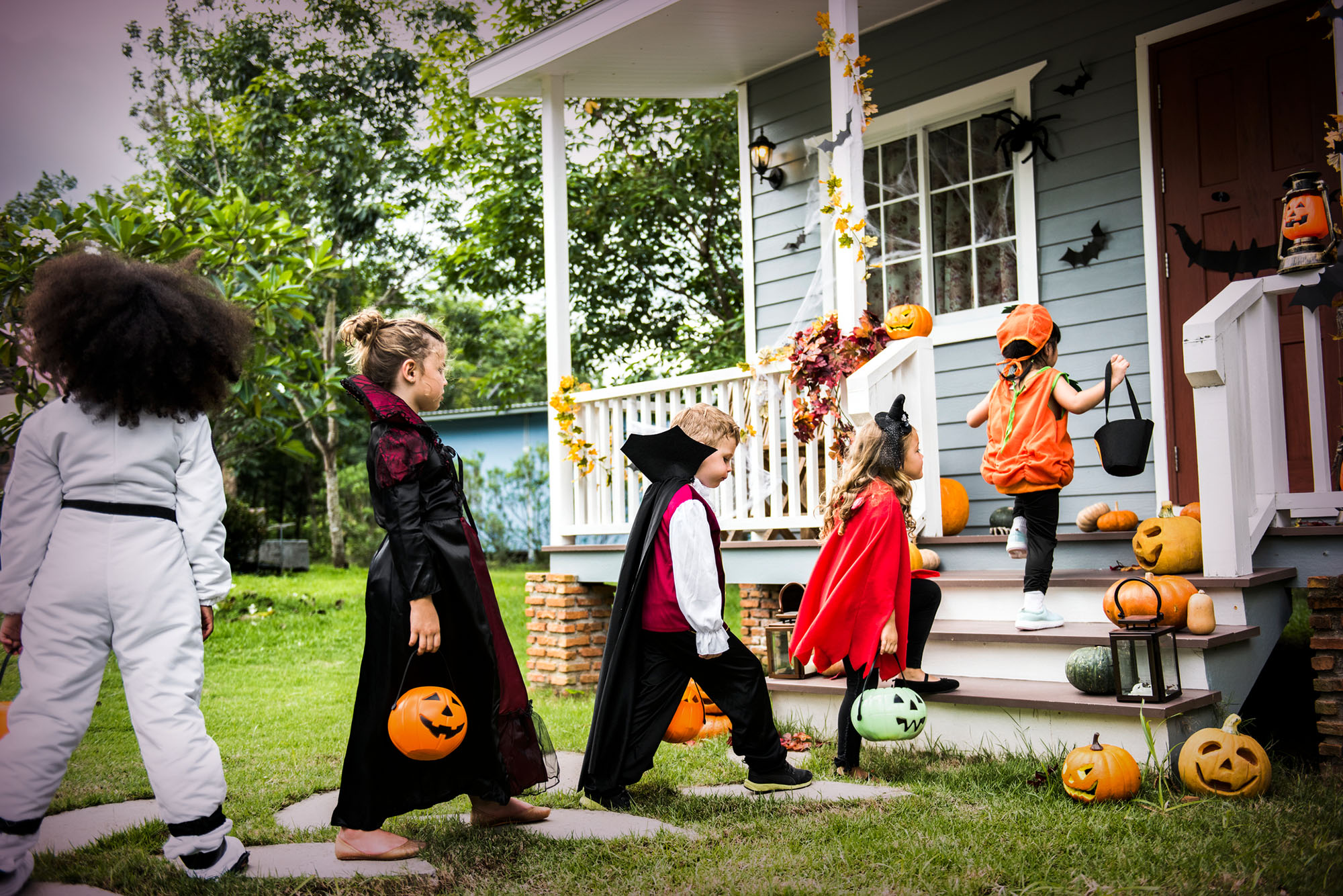 Trick-or-treaters in costumes approaching the front door of a house